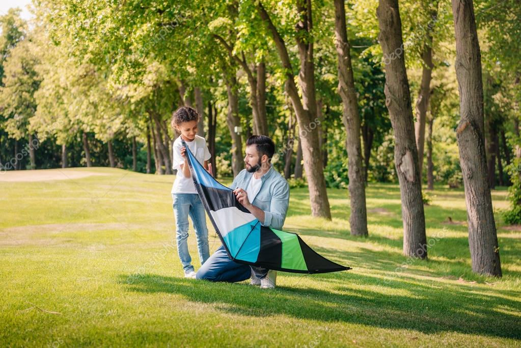 father helping daughter with kite