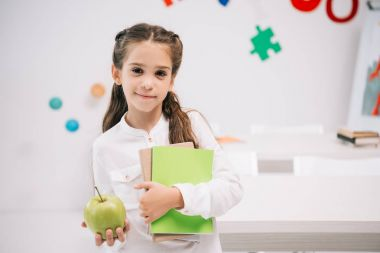 Schoolgirl with apple and textbooks