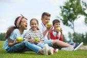 Děti jíst jablka v parku