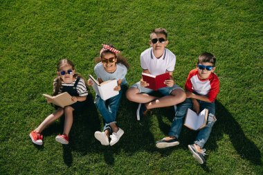 Children reading books in park