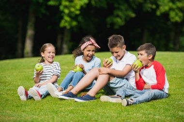 Children eating apples in park