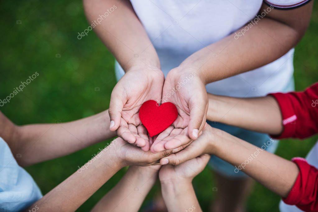 Children holding heart symbol