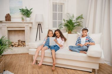 Kids with digital devices at home