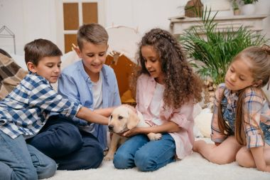 multiethnic children with labrador puppy