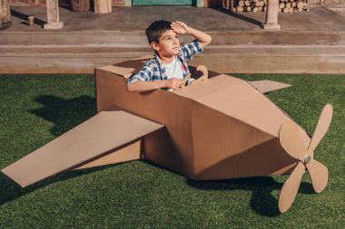 boy in cardboard airplane