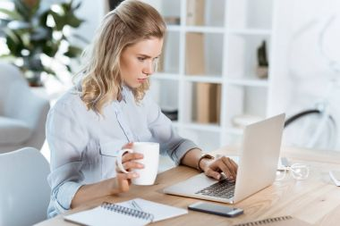 businesswoman typing on laptop in office