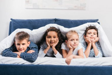 multicultural children lying in bed
