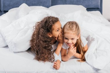 multicultural girls gossiping in bed