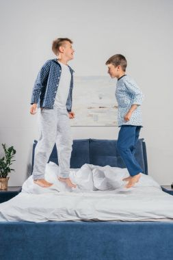 little boys jumping on bed