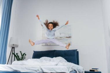 african american girl jumping on bed