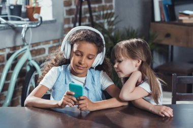 multicultural girls with digital devices