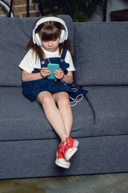 girl in headphones using smartphone