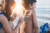 dívka použití sluneční krém na chlapce