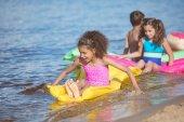 Fotografie Multikulti-Mädchen schwimmen auf aufblasbaren Matratzen