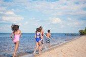Photo children running on sandy beach