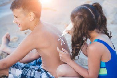 girl applying sun cream on boy