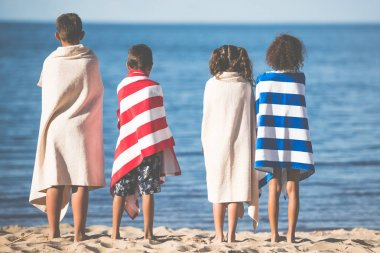 kids in towels standing on beach