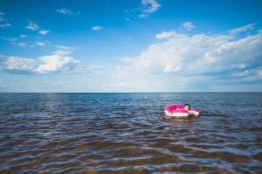 Boy swimming on inflatable doughnut