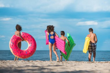 kids with inflatable mattresses on beach