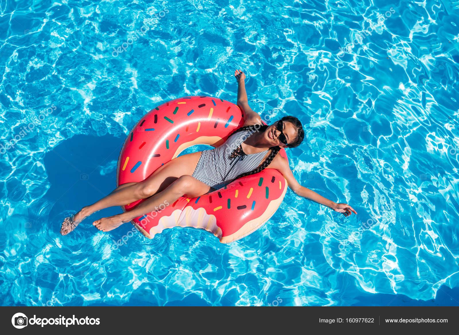 Aziatische vrouw op opblaasbare donut in zwembad for Zwembad aanschaffen