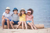 Fotografie multiethnic children sitting at seaside