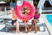 Fotografia Donna multietnica con ciambella gonfiabile vicino piscina