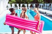 Fotografia Donna multietnica con materasso gonfiabile vicino piscina