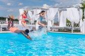 mnohonárodnostní lidí skákání do bazénu