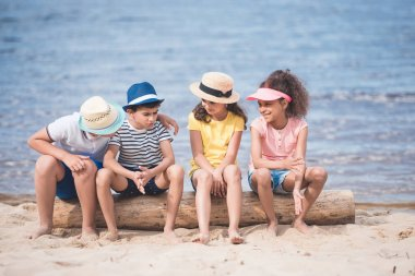 multiethnic children sitting at seaside