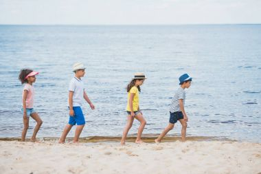 multicultural kids walking on beach