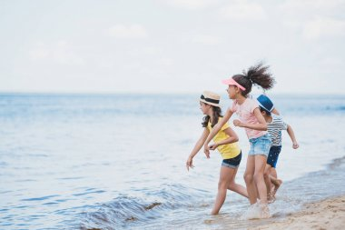 multicultural kids throwing stones at seaside
