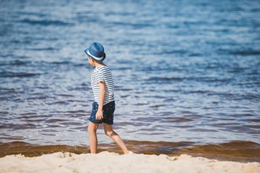 boy walking on sandy beach