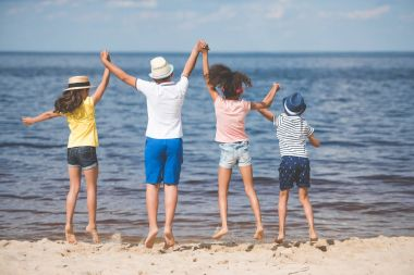 children jumping at seaside