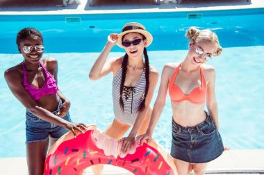 Multiethnic women with inflatable donut near pool