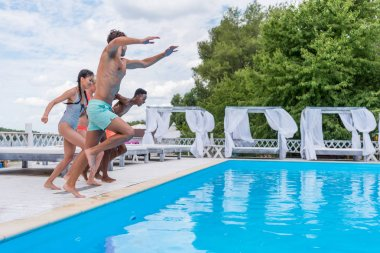 multiethnic people jumping into swimming pool