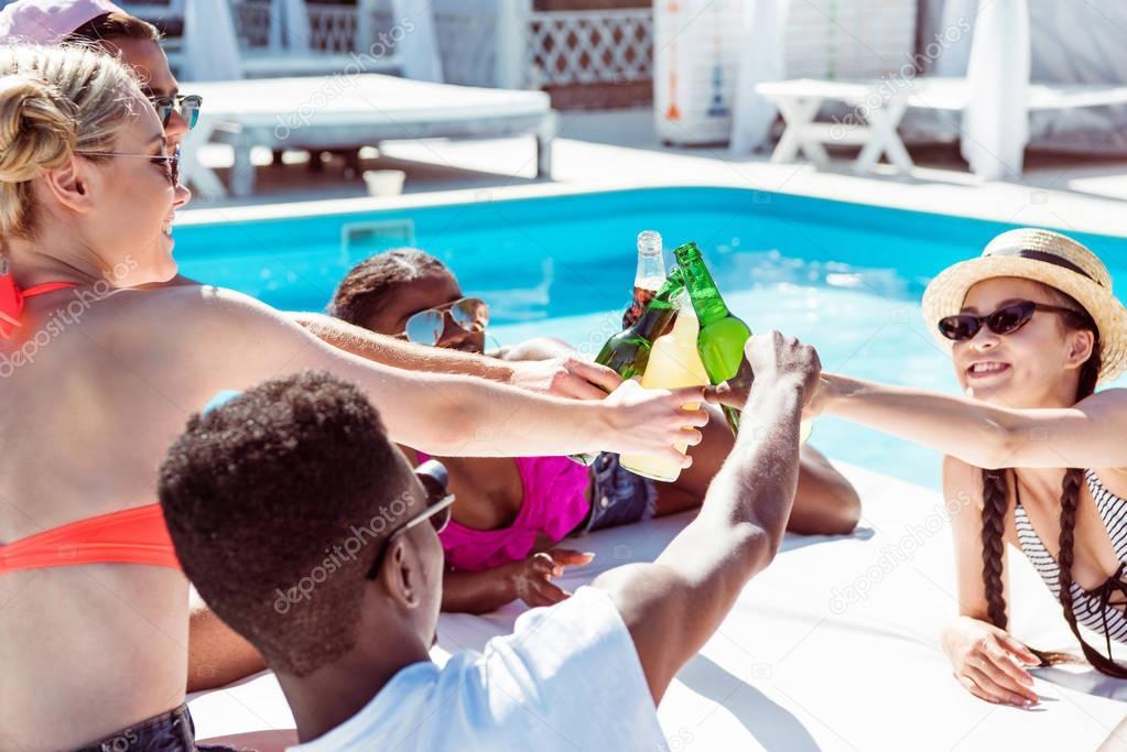 Multiethnic friends near pool at resort