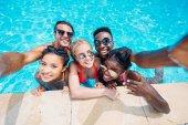 mnohonárodnostní lidí užívajících selfie v bazénu