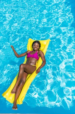 African american woman floating on inflatable mattress in swimming pool stock vector
