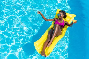 African american woman floating with cocktail on inflatable mattress in swimming pool stock vector