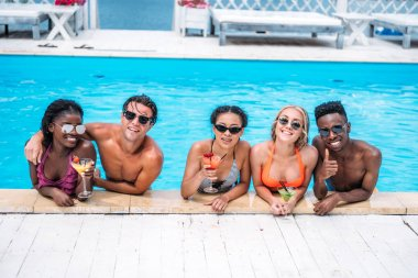 Group of young happy multiethnic people with cocktails in swimming pool stock vector