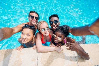 multiethnic people taking selfie in pool
