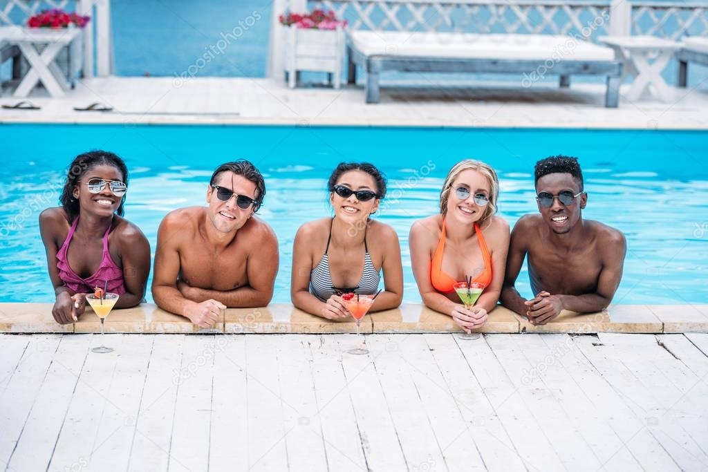multiethnic people with cocktails in swimming pool