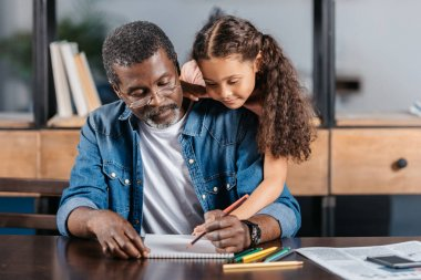 African american man drawing with daughter