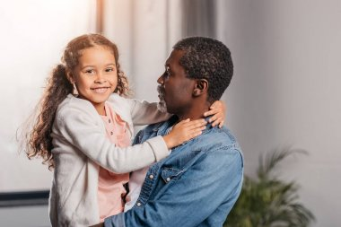 african american man holding daughter