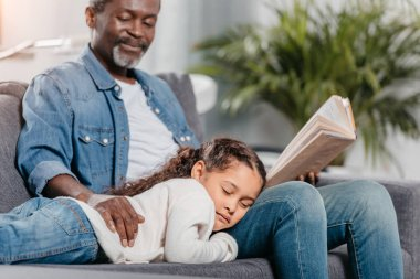 Man reading book for daughter at home