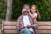 Fotografie Mädchen schließt Augen ihres Großvaters