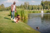 Fotografie granddaughter and grandfather feeding duck