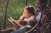 girl and grandfather reading book