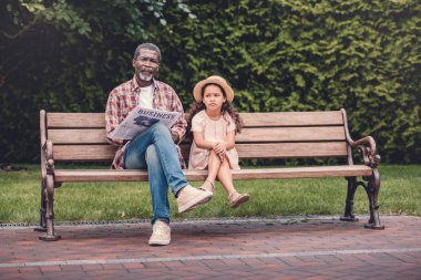 Granddaughter and her grandfather sitting on bench