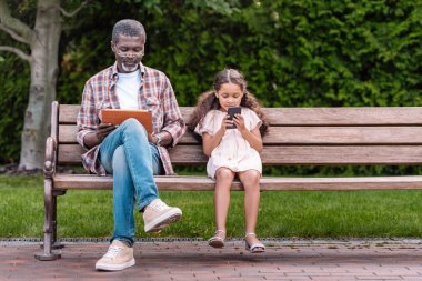 girl and grandfather using digital devices